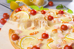 Pizza with seafood red fish, salmon, shrimp, tomatoes, still life, cheese, stretches, shoulder, slice, rises Royalty Free Stock Image
