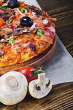 Pizza served on wooden table Royalty Free Stock Photo