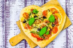 Pizza shape heart wooden background Royalty Free Stock Images