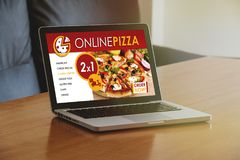 Pizza shop website in a laptop screen, on a wooden table. Stock Image