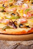 Pizza with shrimp, mussels and octopus closeup on table Royalty Free Stock Images