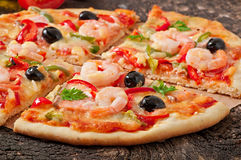 Pizza with shrimp, salmon and olives Stock Images