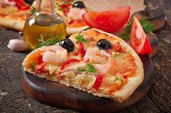 Pizza with shrimp, salmon and olives Stock Image