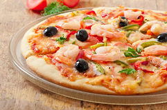Pizza with shrimp, salmon and olives Stock Photography