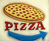 Pizza Sign. A rustic, distressed, hand painted sign for pizza with an arrow showing which way to go for ordering Royalty Free Stock Image