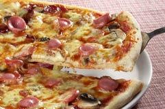 Pizza slice. On a shovel over checked cloth royalty free stock photos