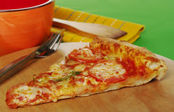 Pizza Slice. A slice of a pizza on wooden board with cutlery, bowl and table mat (Selective Focus Stock Images