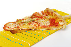Pizza Slice. Vegetarian pizza slice on wooden spatula and yellow table mat on white background (Selective Focus Royalty Free Stock Photography