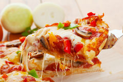 Pizza slice. A Slice of supreme pizza being lifted up stock photography