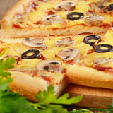 Pizza slice. Pizza with mushrooms slice on the kitchen table with greens on the front royalty free stock photos