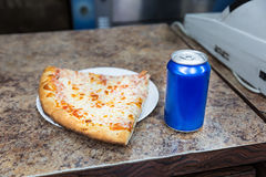Pizza slice and bank of soda. On a counter stock photos