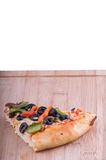 Pizza slice on chopping board vertical. Vegetarian pizza piece on a chopping board, topping include olives tomatoes, pepper and cheese stock image
