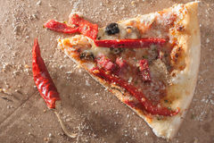 Pizza Slice. Close up of a hot italian pizza slice with red pepper royalty free stock image