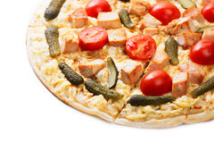 Pizza slice close up. Close up of sliced pizza with tomatoes, meat and gherkins stock images