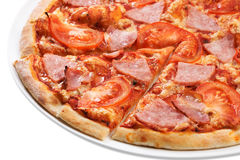 Pizza slice close up. Close up of sliced pizza with tomatoes, meat and ham royalty free stock images