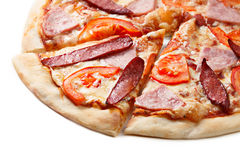 Pizza slice close up. Close up of sliced pizza with tomatoes, meat and sausages royalty free stock photos