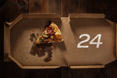 Pizza slice 24 in the in delivery box. Pizza slice in the in delivery box with 24 time text on the wood royalty free stock images