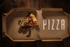 Pizza slice in the in delivery box on the wood royalty free stock images