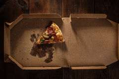Pizza slice in the in delivery box on the wood royalty free stock photography