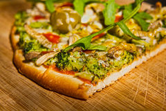 Pizza Slice. Homemade vegetarian pizza on a wooden platter royalty free stock photo