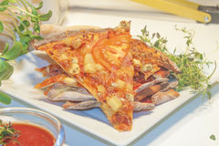 Pizza slice. A pile of pizza slices on a white plate, between herbs and tomatoes stock images