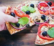 Pizza and slice of pizza in hand. On the table stock photos