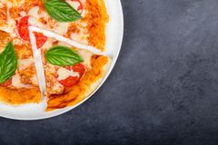 Pizza with slice on the plate. Pizza margherita with slice on the black background with space for recipe. Top view Stock Image