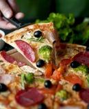 Pizza Slice. With salami, broccoli, tomato, olives royalty free stock image