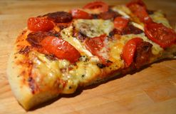 Pizza slice. Pizza with salami tomatoes and cheese on a wooden board royalty free stock images