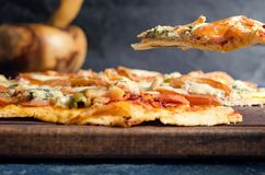 Pizza slice with tomato, chicken and blue cheese. On wooden table royalty free stock photos
