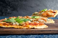 Pizza slice with tomato, chicken and blue cheese. On wooden table royalty free stock photo