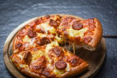 Pizza slice on wooden tray / delicious tasty fast food italian traditional pizza cheese. With Mozzarella , Smoked pork sausage , Pineapple ham on topping sauce royalty free stock images