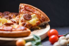 Pizza slice on wooden tray and tomato chilli basil leaf on the dark / delicious tasty fast food italian traditional pizza cheese. With Mozzarella , Smoked pork stock images