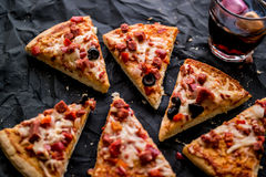 Pizza slices with beverage on a black surface. Royalty Free Stock Image