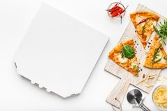 Pizza slices on cutting board and empty cardboard box. Top view, copy space stock photography