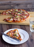 Pizza slices on a plate, white table, cutlery a glass of soda. Pizza with sausage, chicken, corn and cheese, Italian kitchen Royalty Free Stock Image