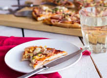 Pizza slices on a plate, white table, cutlery a glass of soda. Pizza with sausage, chicken, corn and cheese, Italian kitchen Royalty Free Stock Images