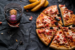Pizza slices with potato wedges and beverage on a black surface Fast food concept. Stock Photo