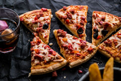 Pizza slices with potato wedges and beverage on a black surface. (Fast food concept) Royalty Free Stock Photo