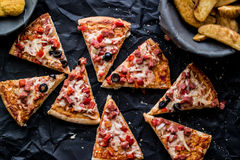 Pizza slices with potato wedges and nuggets on a black surface.(Fast food concept) Stock Photos
