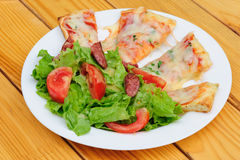 Pizza slices and salad Stock Images