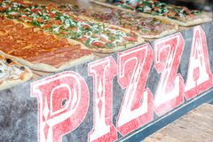 Pizza slices for sale at pizzaria window. Pizza slices for sale at pizzeria window - italian fast food restaurant stock image