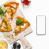 Pizza slices and smartphone with blank screen. Food delivery. Pizza slices and smartphone with blank screen on white background, top view royalty free stock photos