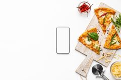 Pizza slices and smartphone with blank screen. On white background, top view stock photography