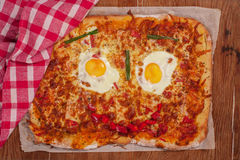 Pizza smiling face on wooden table royalty free stock photography