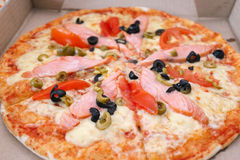 Pizza with smoked salmon and olives in paper box Stock Photos