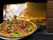 Pizza som kommer ut ur en wood burning pizzaugn. Fotografering för Bildbyråer