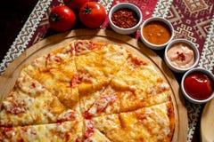 Pizza som ligger på en träplatta på en bordduk med nationella modeller, är därefter fyra såser och tre tomater fotografering för bildbyråer