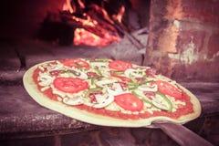 Pizza som skriver in en wood ugn Arkivbilder