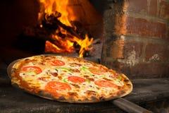 Pizza som skriver in en wood ugn Fotografering för Bildbyråer
